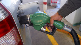 Man serving gasoline with green gun Stock Photography