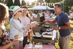 Free Man Serving On Barbeque Stall At Summer Garden Fete Royalty Free Stock Images - 134201659