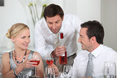 Man serving rose wine. At a dinner party Stock Images
