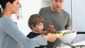 Man serving a salad to his family for lunch