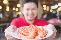 Man is serving steamed shrimp in a white plate. Photo is selective focused at some part of shrimp Stock Image