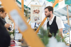 Man serving street food on international cuisine event in Ljubljana, Slovenia. Royalty Free Stock Images