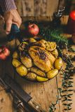 Man serving table with christmas chicken. Man put ready christmas chicken in pan on the table. Ready to eat and to serve. Christmas dinner concept Stock Photography