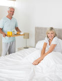Man serving woman breakfast in bed. Mature men serving women breakfast in bed at home Royalty Free Stock Images