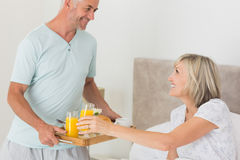 Man serving woman breakfast in bed. Mature men serving women breakfast in bed at home Stock Image