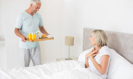 Man serving woman breakfast in bed. Mature men serving women breakfast in bed at home Royalty Free Stock Image