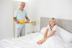 Man serving woman breakfast in bed. Mature men serving women breakfast in bed at home Stock Photo