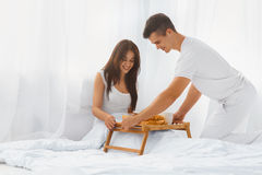 Man serving woman breakfast in bed. Young attractive men serving pretty smiling women romantic breakfast in bed in the morning.  Love and care. Relationships Stock Photo