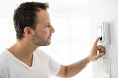 A man set the thermostat at house. Man set the thermostat at house royalty free stock images