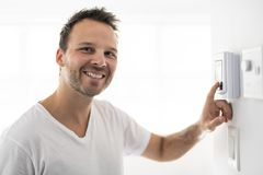 A man set the thermostat at house. Man set the thermostat at house stock photography