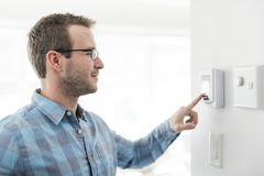 A nice man set the thermostat at house. A man set the thermostat at house stock image