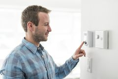 A nice man set the thermostat at house. A man set the thermostat at house stock images