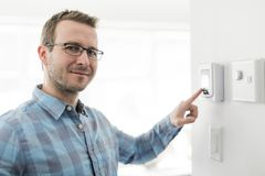 A nice man set the thermostat at house. A man set the thermostat at house royalty free stock photos