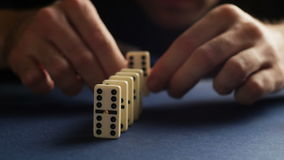 Man set up the domino with hand. Domino effect. 4K stock video