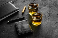 Man set. Whiskey with ice, cigar, wallet and notebook black bar background Royalty Free Stock Image