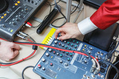 Man sets the audio level on the console audio effects. Stock Photo