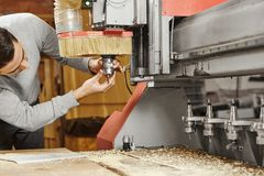 Man sets the cutter in the CNC machine. Device with numerical control. Woodworking industry stock photos