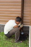 Man sets drainpipe on the wall stock image