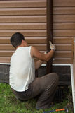 Man sets drainpipe on the wall stock photos