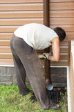 Man sets drainpipe on the wall stock photography