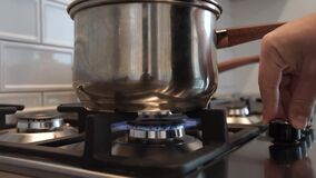 A man sets fire to the burner of a modern stainless steel gas stove and sets the pan for cooking.