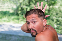 Man sets himself horns. Tanned, bearded man grimacing set himself horns with his hand, close-up Stock Image