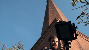 Man sets retro camera next to the chimney. Man sets an old retro camera next to the chimney stock footage