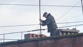 Man sets on a rooftop TV antenna. The man on the roof. Man sets on a rooftop TV antenna stock footage