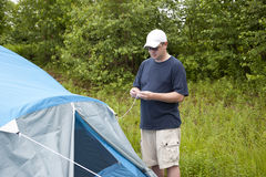 A man sets up his tent in the woods Royalty Free Stock Photo