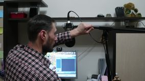 A man sets up a microphone on the computer at home. A man sets up a microphone on the computer