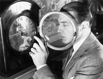 Man setting a clock. (All persons depicted are no longer living and no estate exists. Supplier grants that there will be no model release issues Stock Photos