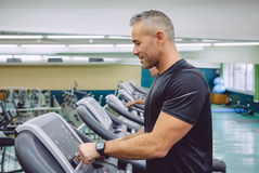 Man setting control panel of treadmill for training Royalty Free Stock Image