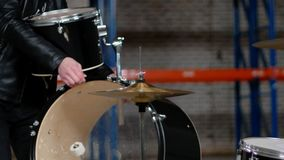 A man setting the drum kit together for the repetition. Mid shot