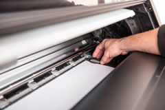 Man setting the printer to the width of the paper Stock Photos
