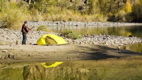 Man setting up his tent for camping. Man setting up his yellow tent for camping on the bank of a mountain river stock video