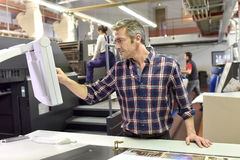 Man setting up a printing machine. Man working on printing machine in print factory Royalty Free Stock Photography