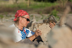Man Setting Up Stone Pile. OTTAWA, CANADA – AUGUST 18: Dan Davis of Canada balancing stones while participating in the International Stone Balance Festival at Stock Photos