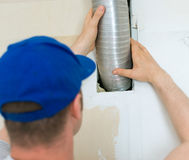 Man setting up ventilation. Stock Images