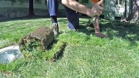 Man setts up lawn hitting an ax on the grass. Setting new lawn stock video footage