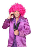 Man in a seventies costume. And crazy wig on cellphone Royalty Free Stock Images