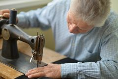 Man with sewing machine Royalty Free Stock Images