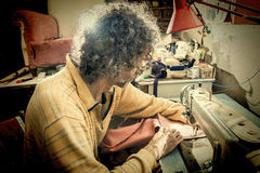 Man at the sewing machine Stock Photography