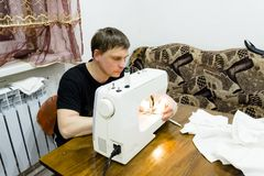 A man sews on a sewing machine stock photography