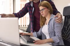 Man sexually harassing female colleague at work. Businessman sexually harassing female colleague during working hours at a workplace royalty free stock image
