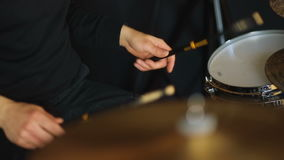 Man in shadeless black style playing on the drums side-view stock video
