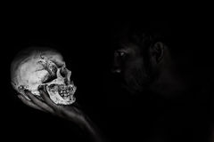 Man in shadow stare human skull that hold in hand Royalty Free Stock Photo