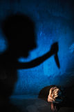 Man shadow stubbing with knife naked woman. Rape, violence and murder concept. Royalty Free Stock Images