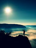 Man shadowing eyes. Alone tourist on cliff edge and watching into deep valley Royalty Free Stock Photo