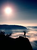 Man shadowing eyes. Alone tourist on cliff edge and watching into deep valley Royalty Free Stock Images