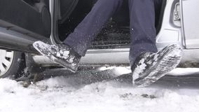 The man shakes off the snow sitting in the winter car, slow motion, outdoor stock footage